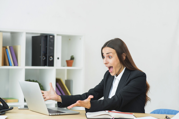 A woman in her business attire and looking in her laptop with a surprise and amaze look